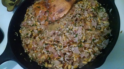 Add chopped yellow raisin, crickets, pine nuts, salt, and rice. Stir to coat rice in oil, cooking about 1-2 min.